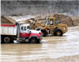 Dump truck and bulldozer in dirt mine with standing water