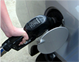 Close-up of hand holding gasoline pump nozzle in a car's gas tank