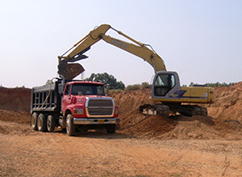 Track hoe loads a dump truck at a sand and gravel mining operation