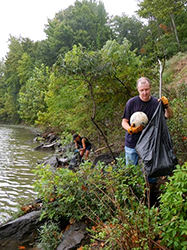 Two people participate in Arkansas's Great River Cleanup by picking up trash along the Arkansas River bank