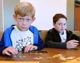 Two boys work a water habitat puzzle activity
